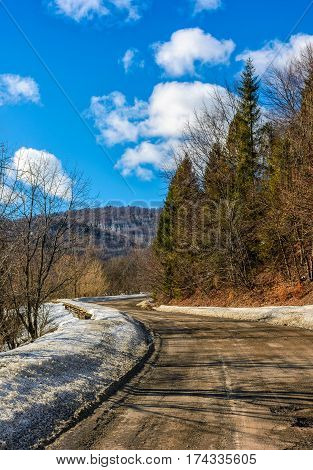 spring has come. last days of winter landscape. countryside curve road with snow on a side passes through forest in mountains