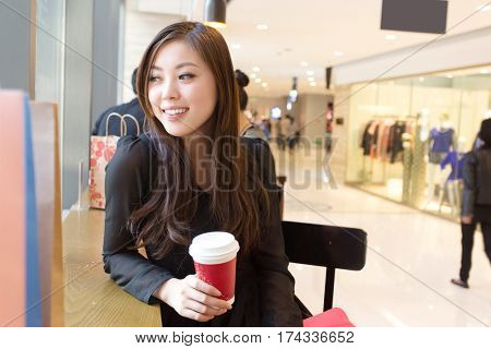 young beautiful chinese woman shopping in modern shopping mall