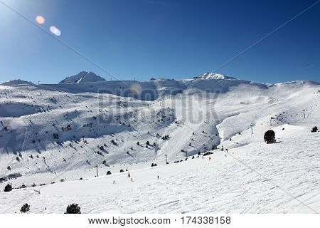 Fresh ski slopes and mountains in sunny day in Andorra