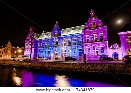 KAMPEN, NETHERLANDS - December 10, 2016: Illuminated facade of a historic building along a canal in Holland. Long exposure photo. Kampen, Overijssel - Netherlands.