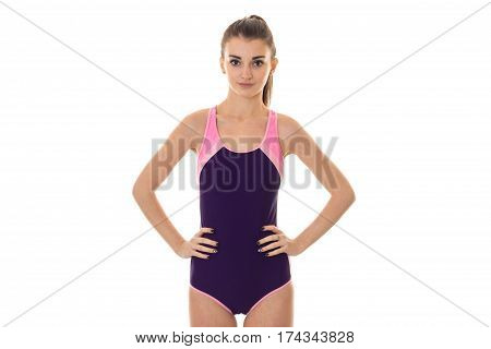 young beautiful slender girl in a body suit keeps his hands on the sides of isolated on white background