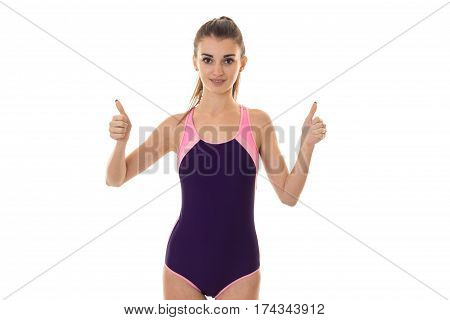 young beautiful slender girl in body swimsuit looks into the camera and shows the class hands isolated on white background