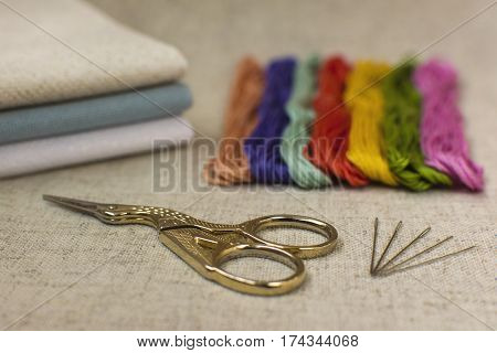 Close-up of the embroidery and cross-stitch kit on a natural linen background. Scissors needles colored threads and canvas.