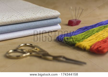Cross-stitch set for embroidery consisting of needles colourful threads canvas and scissors. Focus on the sheets of canvas.