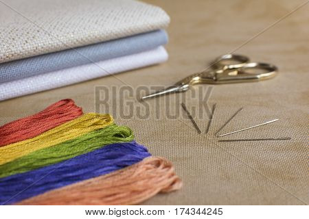 Embroidery and cross-stitch kit on a natural linen background. Focus on the needles.