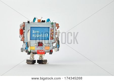 Bon appetit concept robotic chef character with fork and knife in arms. Retro style cyborg monitor face, blue screen wishing enjoy your meal. Gray paper background copy space.