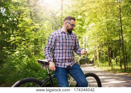 Modern Man Sitting On Bike At Park Thinking