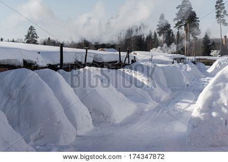 snow-covered garages in the village in Russia. Chimneys in the garage. Large drifts. Cooperative garages in snow.