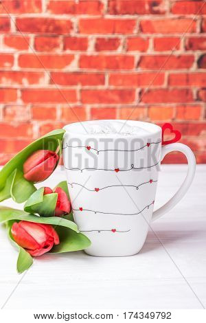 Homemade vanilla coffee latte with love, red heart and spring tulips. Background brick wall