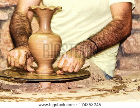 Man´s hands forming clay vase on the pottery wheel