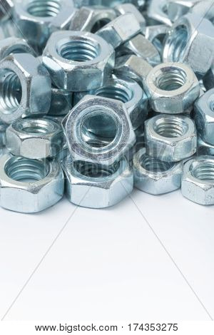 Macro Image Of Pile Of Grey Metal Nuts Over White Background
