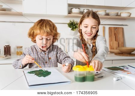 What would we do next. Admirable enthusiastic bright children having fun painting things while spending the weekend together and sitting at the table in a kitchen