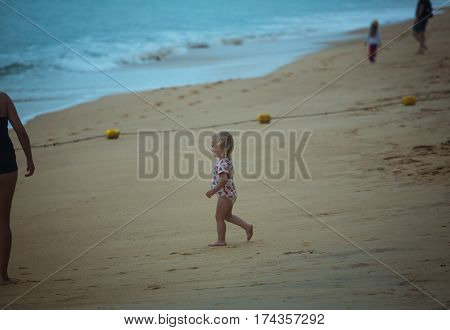 Side view of little smiling cute girl walking on sandy beach to the ocean against splashing waves