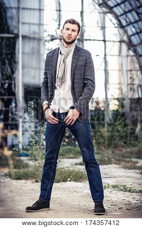 Fashion shot: portrait of a handsome young man wearing jeans shirt jacket and scarf