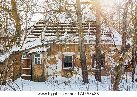 Old abandoned empty wooden rural brown house with broken roof and windows covered with fresh white snow. Village in Ukraine. Horizontal color image.