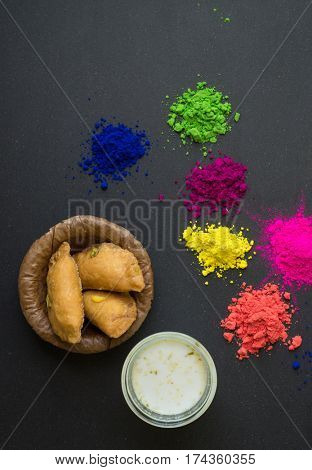 Holi- festival of colors. Gujeeya and flavoured milk with splash of powder colors. Holi festival is celebrated in India by consuming milk with Bhang and splashing colors in each others.