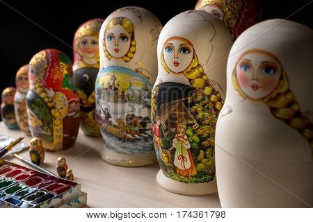 Set of nested dolls - russian matryoshkas on the table at dark workshop, selective focus