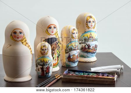 Set of wooden nested dolls - russian matryoshkas on the table at workshop, selective focus, white background