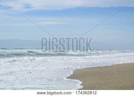 Sea waves with foam at the shore of national park Cabo de Gata near Almeria Andalusia Spain.