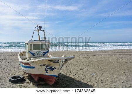 CABO DE GATA SPAIN - FEBRUARY 9 2016: A colored fishing boat at the shore of national park Cabo de Gata near Almeria (Andalusia Spain) and sea waves on the background.