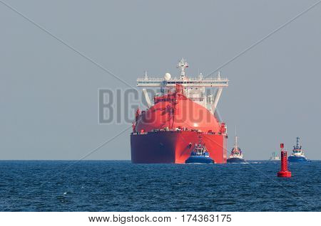 RED GAS CARRIER -  Red tanker at sea by tugs