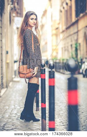 Women's fashion. Beautiful young woman standing in the street in the city. attractive and youthful look. Dress, boots and bag on her shoulder. Rome, Italy.