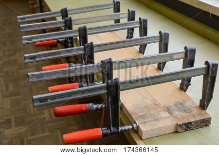 Many screw clamps press freshly glued wooden board - close-up