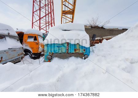 Old mobile construction crane with hook and some trucks are in the snowdrift
