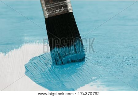 brush cover the wood with a thick layer of bright blue paint