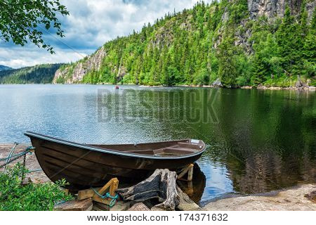 Wooden boat on the lake bank on forest background and blue sky reflecting in the surface of the river Norway