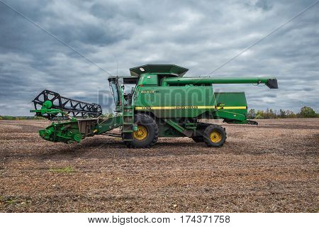 Kiev Region Ukraine - October 6 2013: John Deere 9610 Maximizer combine harvester on the field after soybean harvesting with cloudy sky on the background