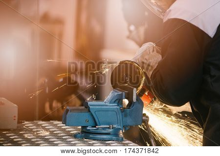 Mechanic In Protective Gloves Cutting Metal