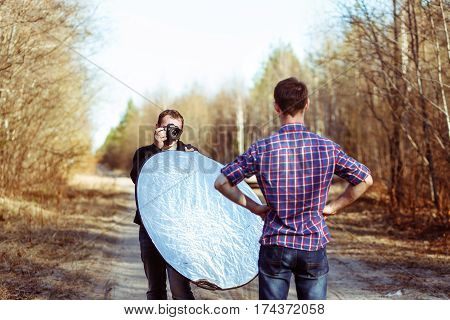Photographer Photographing Male Model in Forest. Backstage of Fashion Photoshoot by Professional Photographer with DSLR Camera and Reflector.