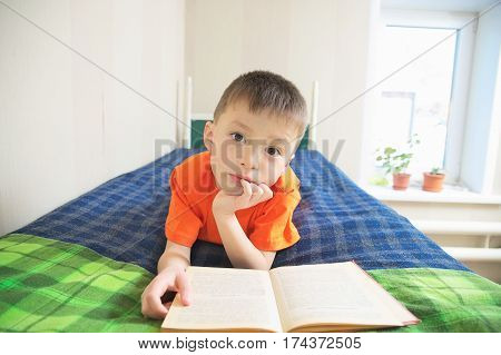 boy reading book lying on bed, children education child portrait with book education concept interesting storybook
