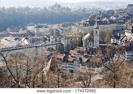 BERN SWITZERLAND - DECEMBER 26 2015: Aerial view of city shows a significant density of development of the Old Town. Church tower and the stone bridge that can be seen during winter day with no snow