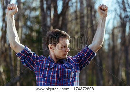 Slim man hipster in plaid shirt shows his muscles in forest. Self-irony concept.
