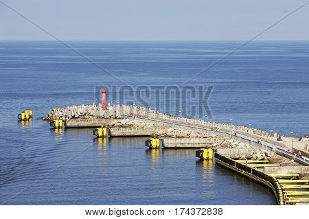 KOLOBRZEG POLAND - JUNE 22 2016: Breakwater with the red lighthouse placed on its end. It was built to protects the waterway to the sea port from the action of the waves