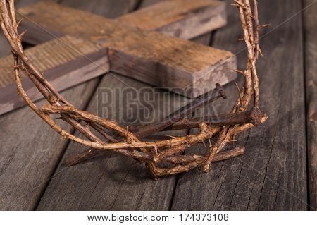 Crown of thorns and nails closeup and cross in background on a wood surface