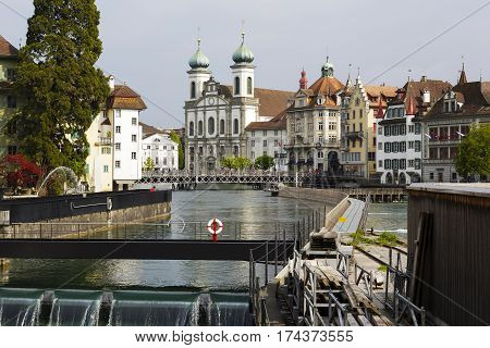 LUCERNE SWITZERLAND - MAY 02 2016: Jesuit church and other buildings and the weir built in the side stream of river Reuss creates landscape of this attractive tourist city.
