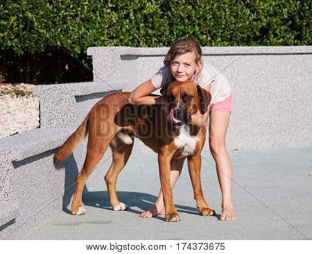 little girl stroking her crossbreed dog in the garden