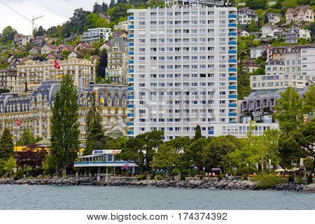MONTREUX SWITZERLAND - MAY 20 2013: High building on the shore of Lake Geneva together with houses that are visible in the background it creates landscape of a city looked like is densely built-up