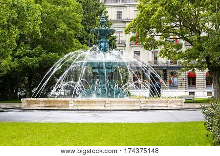 GENEVA SWITZERLAND - MAY 21 2013: Large round and richly decorated fountain located in English Garden among greenery. Townhouse in the background can be seen