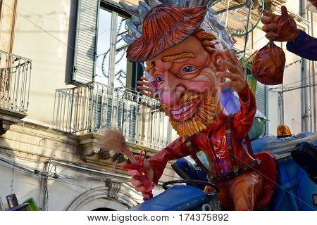 Acireale (CT) Italy - February 28 2017: detail of a allegorical float depicting a man with dress and red hat during the carnival parade along the streets of Acireale.