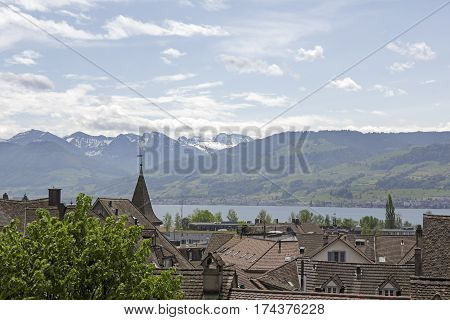 RAPPERSWIL SWITZERLAND - MAY 10 2016: General view towards roofs of the city that are located in the old town. In the background the lake and the mountain range can be seen.