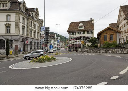 SCHWYZ SWITZERLAND - MAY 09 2016: Roundabout on which goes one car. Buildings and road directional signs and a few people who can be seen in a distance. This is shown on an overcast day.