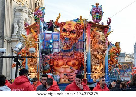 Acireale (CT) Italy - February 28 2017: allegorical float depicting a big devil in a niche on whose walls are depicted other demons faces during the carnival parade along the streets of Acireale.