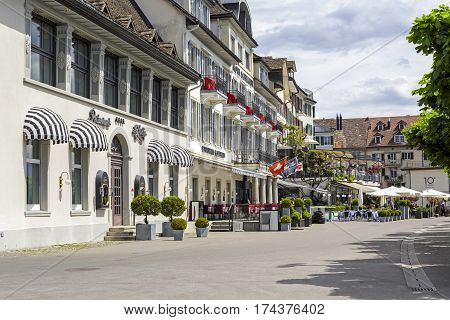RAPPERSWIL SWITZERLAND - MAY 10 2016: Buildings hotels and restaurants along sidewalk that is named a See Quai. There are people who can be seen in restaurants in a far distance