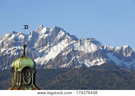 LUCERNE SWITZERLAND - MAY 05 2016: The tower on the historic residential building which is topped with a small mast with an unknown coat of arms. Peak of Pilatus can be seen in a distance