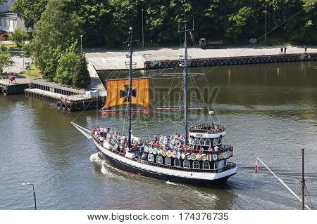 KOLOBRZEG POLAND - JUNE 22 2016: Stylized cruise ship that is named The Pirate enters the port there are many tourists on board who returning from a trip on the waters of the Baltic Sea