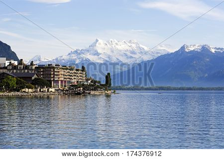 MONTREUX SWITZERLAND - MAY 27 2013: The buildings on the shore of Lake Geneva and the snow-capped mountains as seen in the distance on a bright day